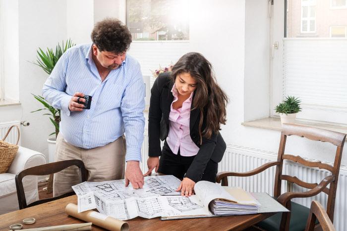 Ralf Gutzki und Jacqueline Gutzki begutachten den Grundriss einer Immobilie